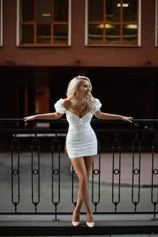 Портрет молодой красивой женщины в белом платье на фоне улицы.