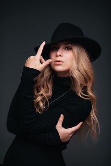Портрет молодой красивой женщины в черной шляпе на черной стене