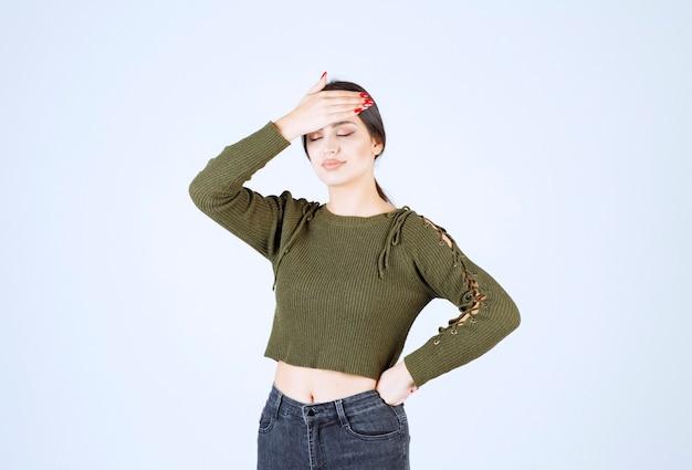Портрет молодой красивой женщины модельной стоя и держа ее за голову.