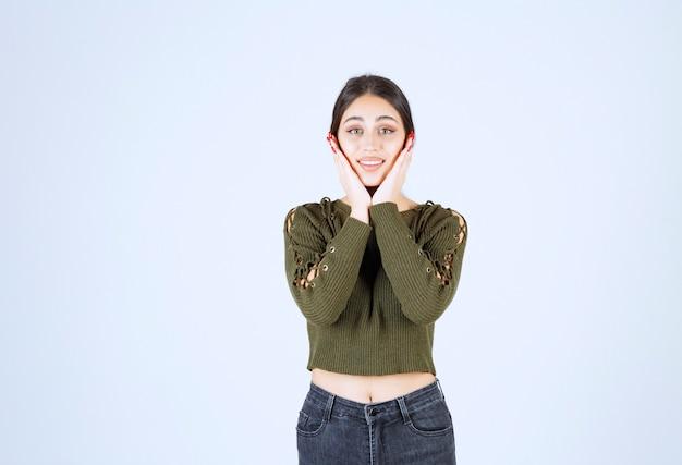 Портрет молодой красивой женщины модельного стоя и позирует над белой стеной.