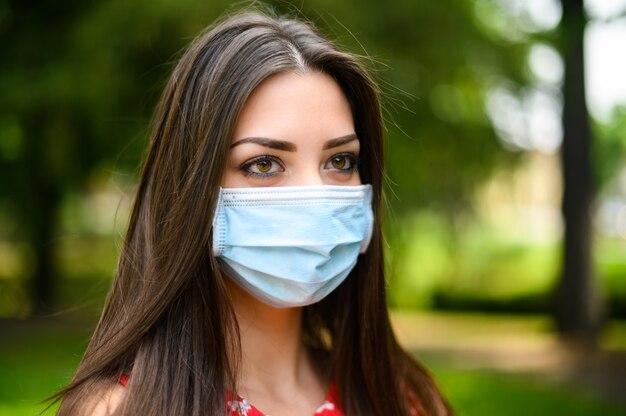 Портрет молодой красивой женщины на открытом воздухе в парке в маске во время коронавируса