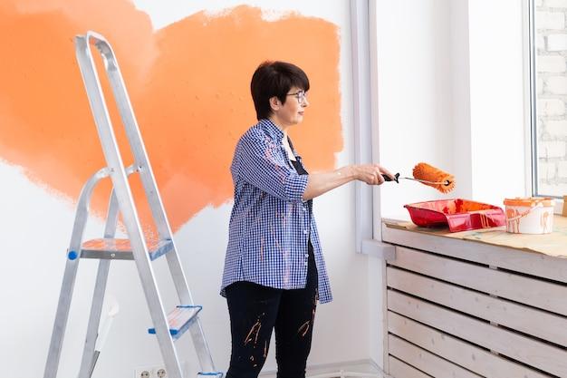 彼女の新しいアパートで壁を描いている若い美しい女性の肖像画