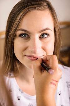 Портрет молодой красивой женщины, получающей макияж от художника