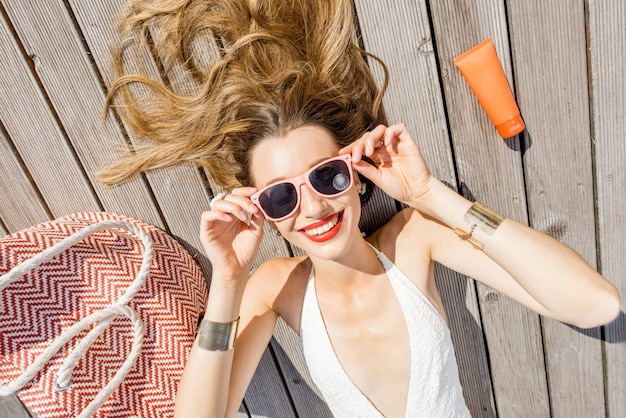 盆地の近くの屋外の木製のプールサイドで夏のものでリラックスした若い美しい女性の肖像画。夏休みと日焼けのコンセプト