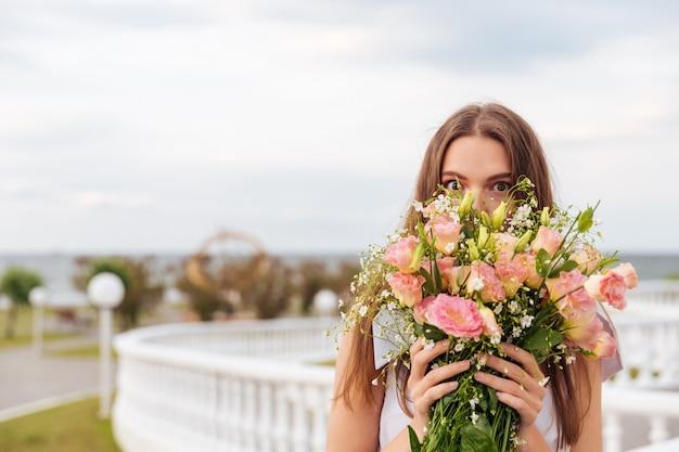 テラスで屋外の花の香りを嗅ぐ若い美しい女性の肖像画