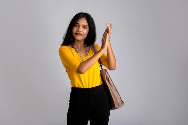 Портрет молодой красивой женщины в стильной одежде с сумочкой или кошельком.