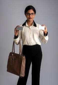 핸드백이나 지갑과 신용 카드를 가진 젊은 아름다운 여자의 초상화