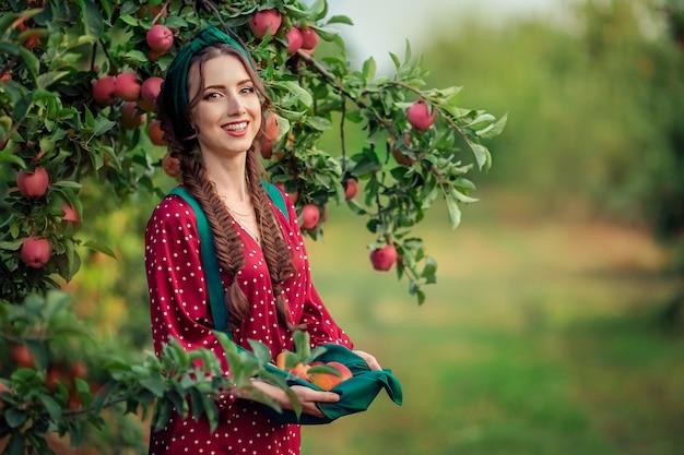 黒い髪と白い歯で熟したリンゴを手に持った若い美しい女性の肖像画。リンゴ園での収穫
