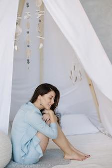 Портрет молодой красивой женщины с темными волосами в постели утром у себя дома