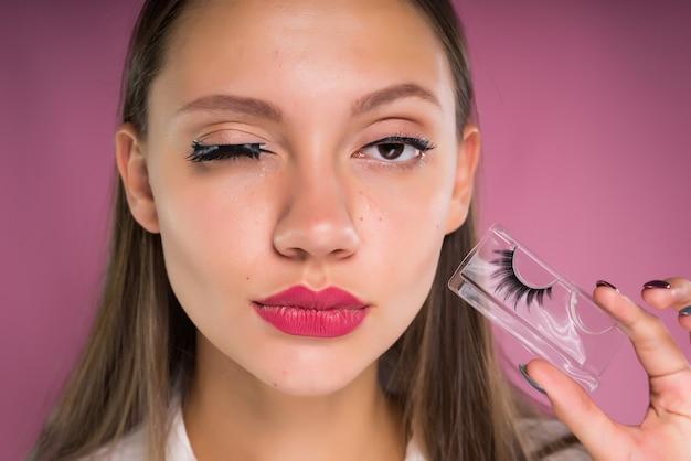 가짜 속눈썹을 가진 젊은 아름 다운 여자의 초상화. 분홍색 배경에 고립
