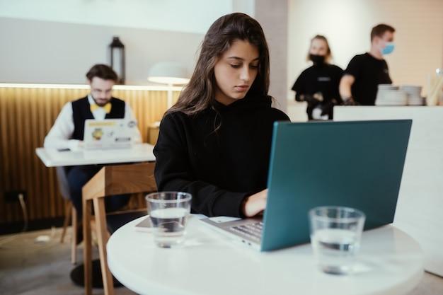 젊은 아름다운 여성의 초상화는 휴대용 랩톱 컴퓨터에서 작동하고 카페에 앉아있는 동안 넷북을 사용하는 매력적인 여성 학생