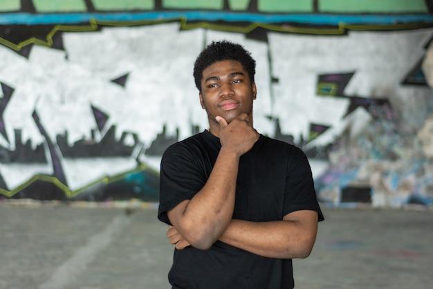 생각하는 젊은 흑인 소년의 초상화입니다. 낙서 벽 배경입니다.