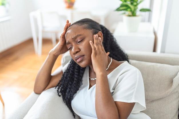 頭痛と背中の痛みで自宅のソファに座っている若い黒人少女の肖像画。慢性的な毎日の頭痛に苦しんでいる美しい女性。副鼻腔の痛みのために頭を抱えている悲しい女性
