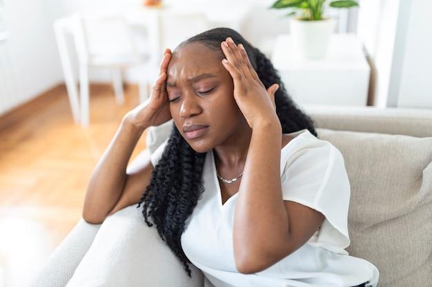 頭痛と痛みで自宅のソファに座っている若い黒人少女の肖像画。慢性的な毎日の頭痛に苦しんでいる美しい女性。副鼻腔の痛みのために頭を抱えている悲しい女性