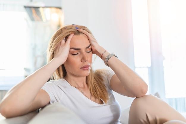 頭痛と片頭痛で自宅のソファに座っている若いブロンドの女性の肖像画。慢性的な毎日の頭痛に苦しんでいる美しい女性。副鼻腔の痛みのために頭を抱えている悲しい女性