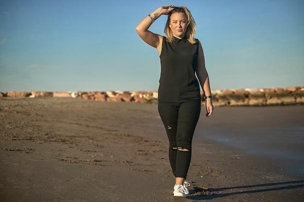 Портрет молодой блондинки, позирующей на море с изношенными модными аксессуарами
