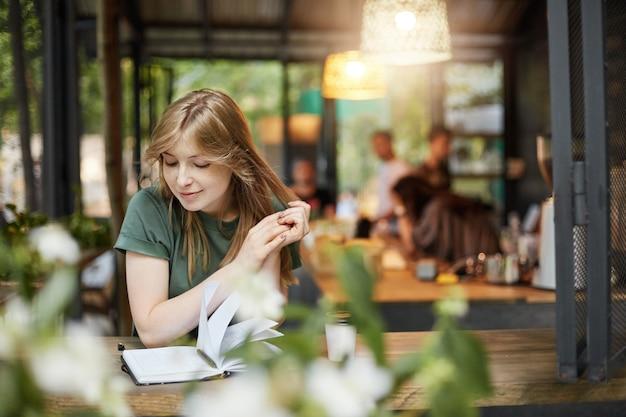웃는 그녀의 클래스를 기다리고 야외 카페에서 커피를 마시는 그녀의 노트를 읽는 젊은 금발 학생 여자의 초상화.