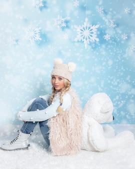 Портрет молодой блондинки с длинными волосами в зимней одежде, сидящей спиной к большому мягкому белому медведю