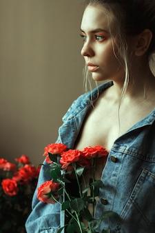 Портрет молодой блондинки с красным макияжем в джинсовой куртке и букетом роз