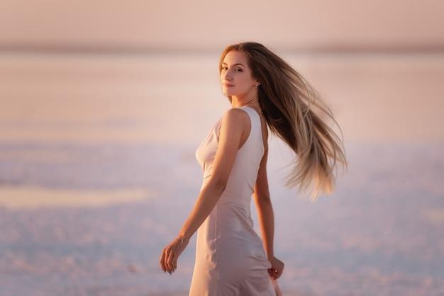 美しい夕日を背景に、風通しの良いパステルピンクの粉っぽいドレスを着た若いブロンドの女性の肖像画。