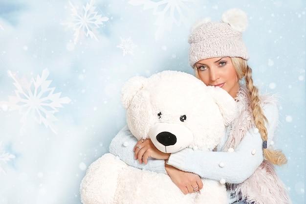 Портрет молодой блондинки с длинными волосами в зимней одежде в объятиях с большим белым медведем.