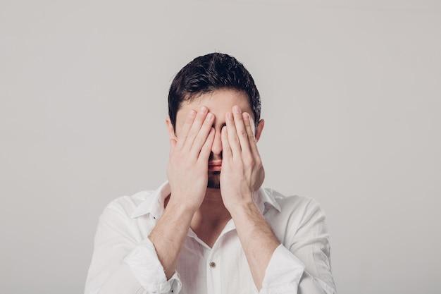 Портрет молодого брюнет в белой рубашке закрывает глаза руками на сером фоне. я не хочу этого видеть. мягкий свет