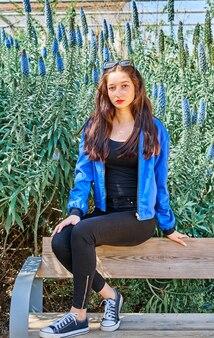 그린 입술과 공원에서 나무 벤치에 앉아 검은 청바지와 젊은 갈색 머리 여자 긴 머리의 초상화