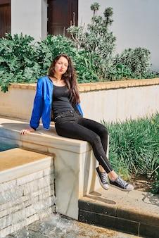 젊은 갈색 머리 소녀, 긴 머리, 페인트 입술과 파란색 재킷과 검은 색 청바지의 초상화, 공원에서 분수 근처에 앉아 프리미엄 사진