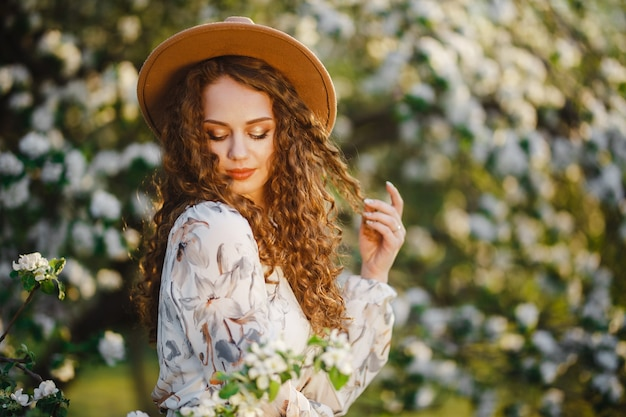 석양에 피 나무 근처 봄 공원에서 그녀의 곱슬 머리를 가지고 노는 젊은 갈색 머리 여자의 초상화. 베이지 색 모자와 흰 드레스를 입은 여성은 꽃 냄새가 좋은 날씨를 즐깁니다.