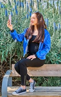 그린 입술과 공원에서 나무 벤치에 앉아 셀카를 만드는 검은 청바지와 젊은 갈색 머리 여자의 초상화