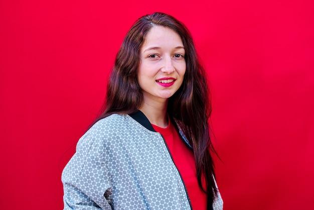 平らな赤い背景に赤い口紅を持つ若いブルネットの少女の肖像画