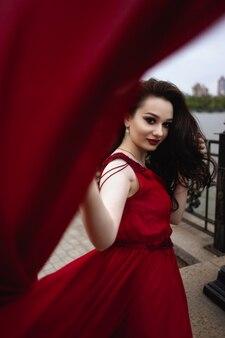 Портрет молодой женщины брюнетка в красном платье с поездом