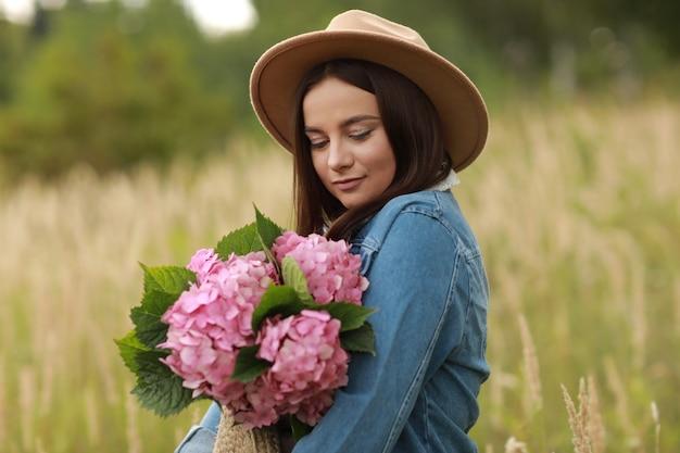 ピンクの花アジサイの花束を保持しているデニムジャケットと帽子の若いブルネットの女性の肖像画、