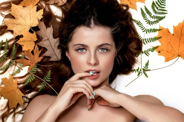 녹색 고사리와 노란색 흰색 배경에 젊은 갈색 머리 여자의 초상화는 그녀의 머리, 피부 및 헤어 케어 개념 주위에 나뭇잎
