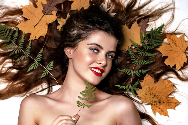 彼女の頭の周りの緑のシダと黄色の葉と白い背景の上の若いブルネットの女性の肖像画