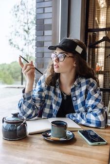 펜과 담요가 있는 레스토랑의 테이블에 앉아 있는 젊은 브루네트 여성의 초상화