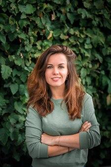 녹색 잎의 배경에 긴 머리를 가진 젊은 갈색 머리 여자의 초상화