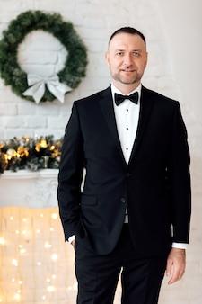 クリスマスの背景に彼のポケットに片手を保持しながらカメラに笑みを浮かべて黒いスーツと蝶ネクタイの若いビジネスマンの肖像画。