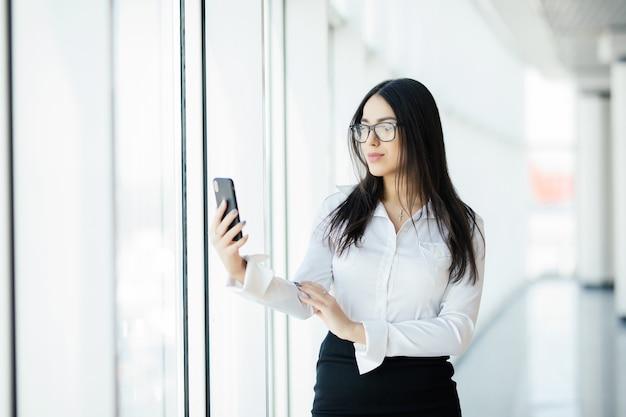 Портрет молодой деловой женщины в очках, набрав текстовый телефон на фоне панорамных окон. бизнес-концепция