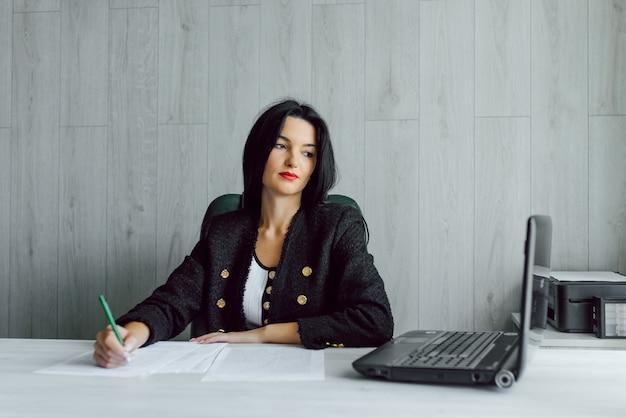 オフィスでラップトップを使用して若いビジネス・ウーマンの肖像画