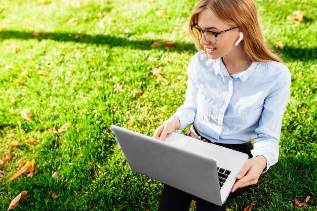 眼鏡をかけて、公園の緑の芝生の上に座って、ノートパソコンとワイヤレスヘッドフォンを使用して作業する若いビジネス女性の肖像画