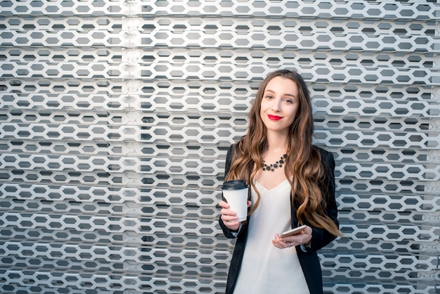 Портрет молодой деловой женщины с телефоном и кофе, чтобы пойти на фоне металлической стены