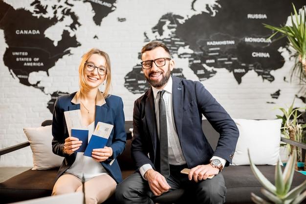 背景に美しい世界地図と旅行代理店のオフィスに座っている若いビジネスカップルの肖像画