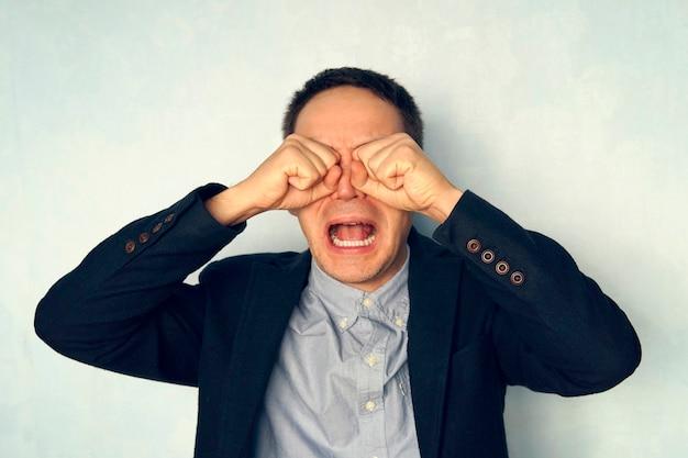 泣いている青年実業家の肖像画。男は子供のように泣きます。スーツを着た男は口を大きく開けて叫ぶ。サイコワーカー。
