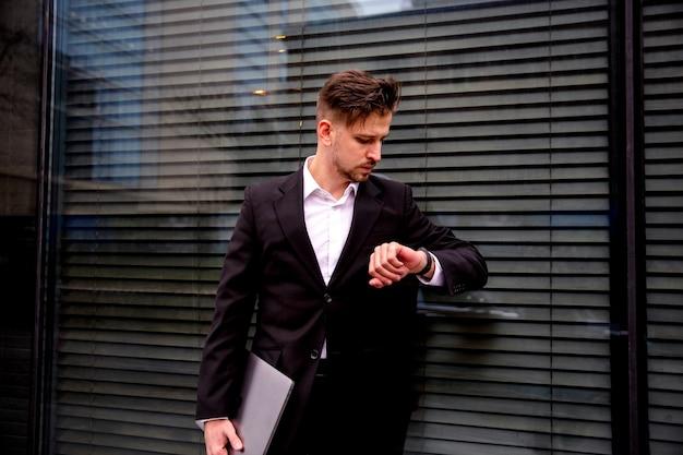 Портрет молодого бизнесмена в бизнес-центре с ноутбуком в руках