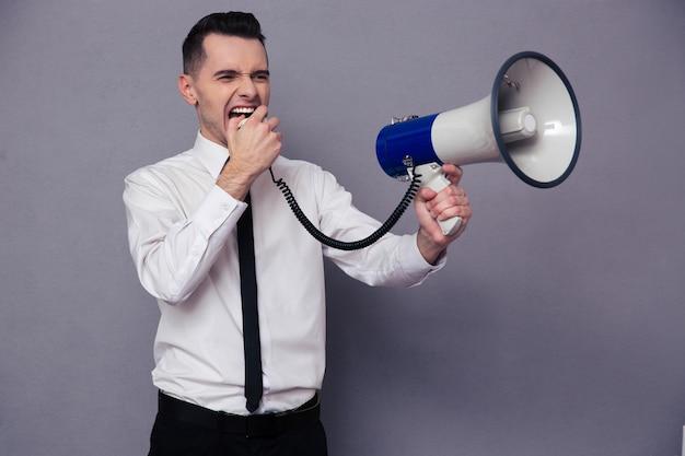 Портрет молодого бизнесмена, кричащего в мегафон над серой стеной