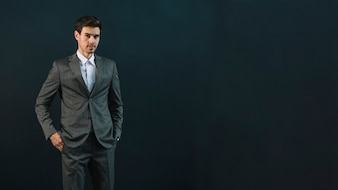 Portrait of a young businessman standing against dark background