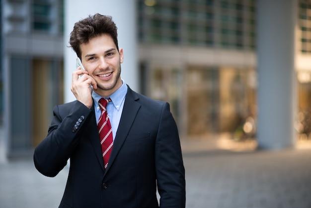 彼のオフィスの前で屋外で電話で話している青年実業家の肖像画
