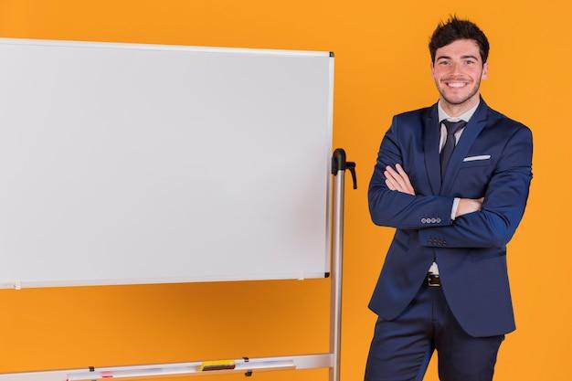 彼の腕を持つ青年実業家の肖像画はオレンジ色の背景に対してホワイトボードの近くに立って交差しました
