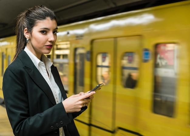 Портрет молодой предприниматель, держа в руке мобильный телефон, глядя